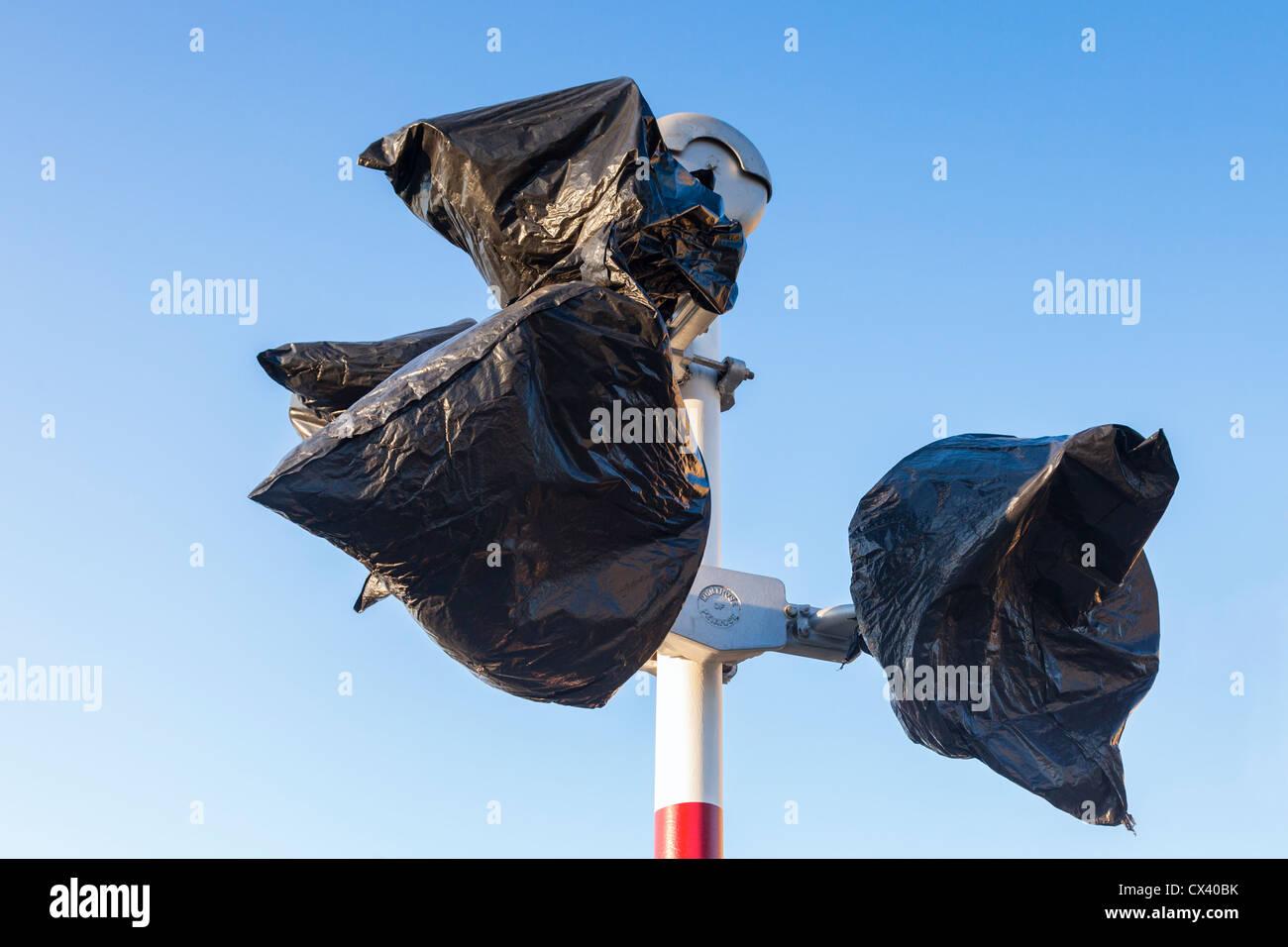 Paso a nivel de luces de advertencia, cubierto con bolsas de papelera de plástico negro. Imagen De Stock