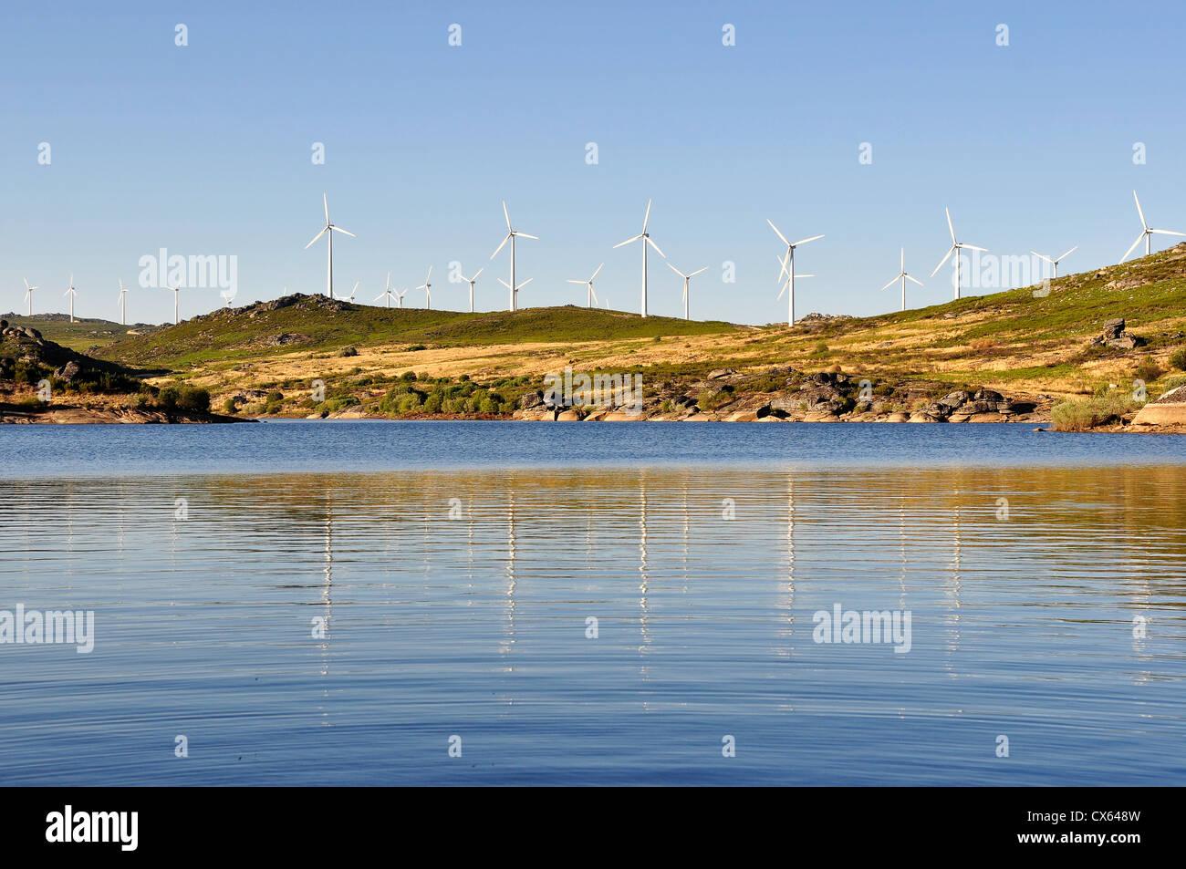 Molino de viento, con varias turbinas eólicas, cerca de un río, produciendo energía verde. Imagen De Stock
