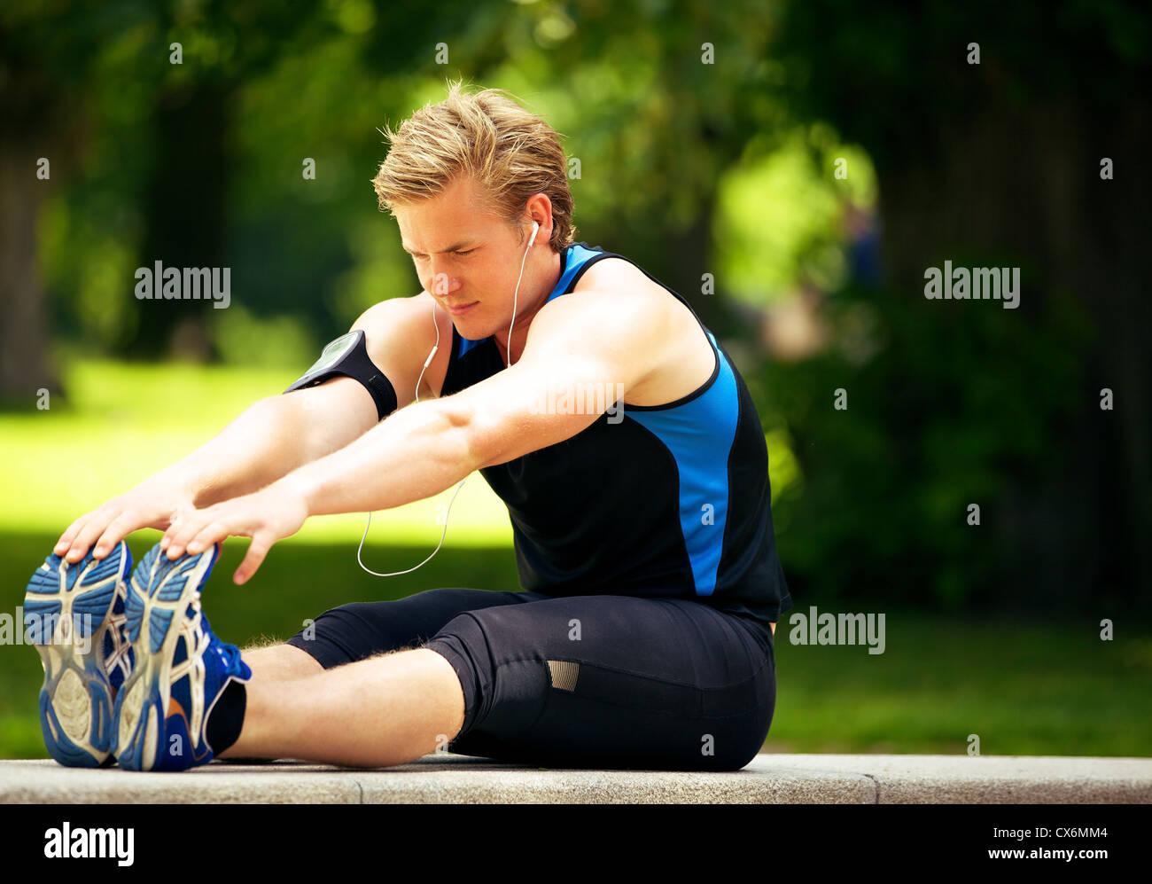 Atractivo atleta haciendo su ejercicio de estiramiento Imagen De Stock