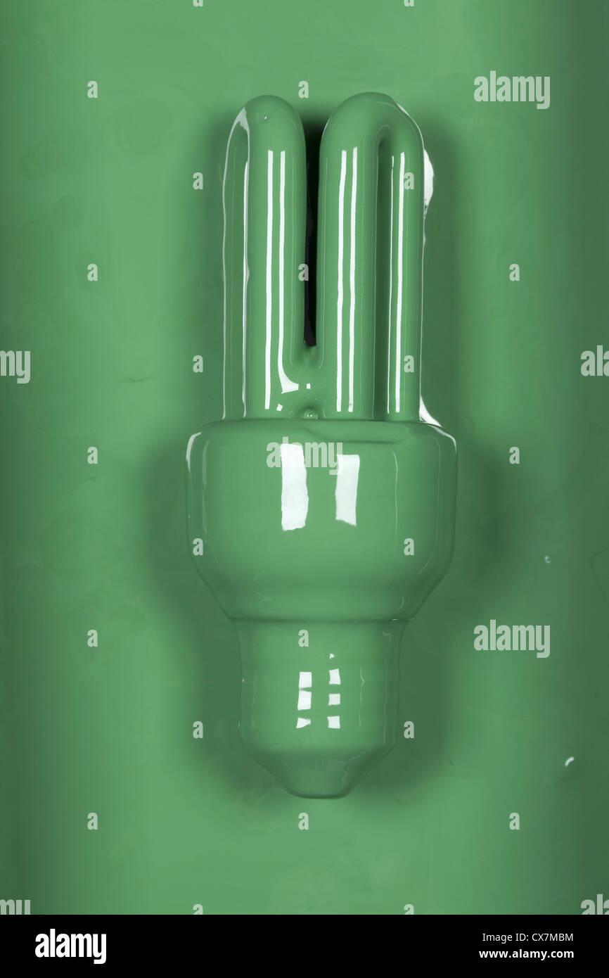 Una bombilla de bajo consumo pintados de verde Imagen De Stock