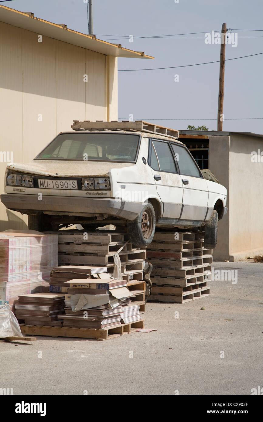 Desglosa viejo coche descansa sobre un conjunto de palets - Garaje de coches ...