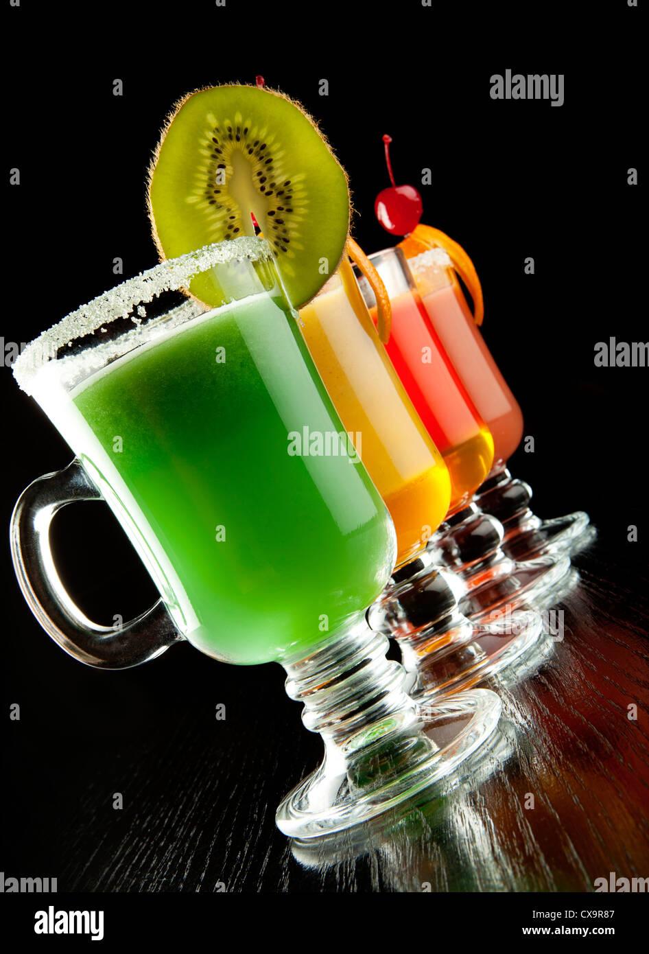 El grupo de cuatro copas de vino con coloridas bebidas cócteles, decorados con frutas y azúcar negra sobre Imagen De Stock
