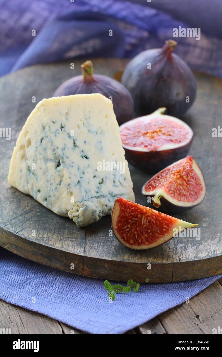 El queso azul y fruta dulce de higos en una placa de madera Imagen De Stock