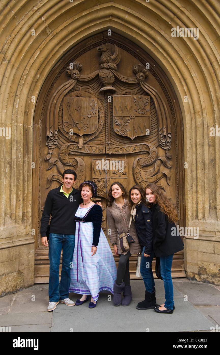 Los turistas representan fuera de la puerta de la Abadía de Bath con la mujer en Regency costume durante el Imagen De Stock
