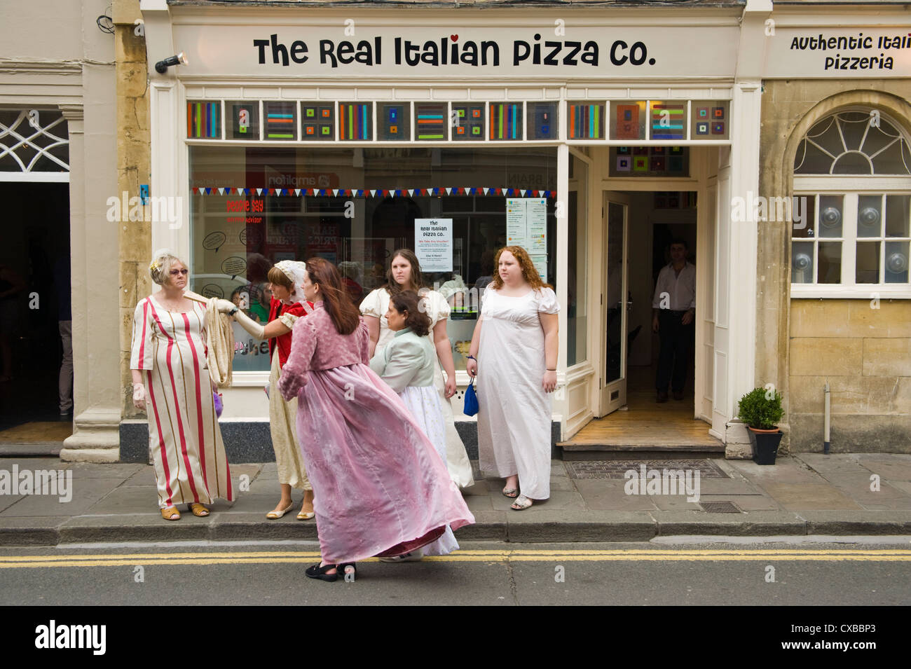 La mujer en Regency traje de baño fuera de restaurante de pizza en el centro de la ciudad durante el 2012 Festival Imagen De Stock