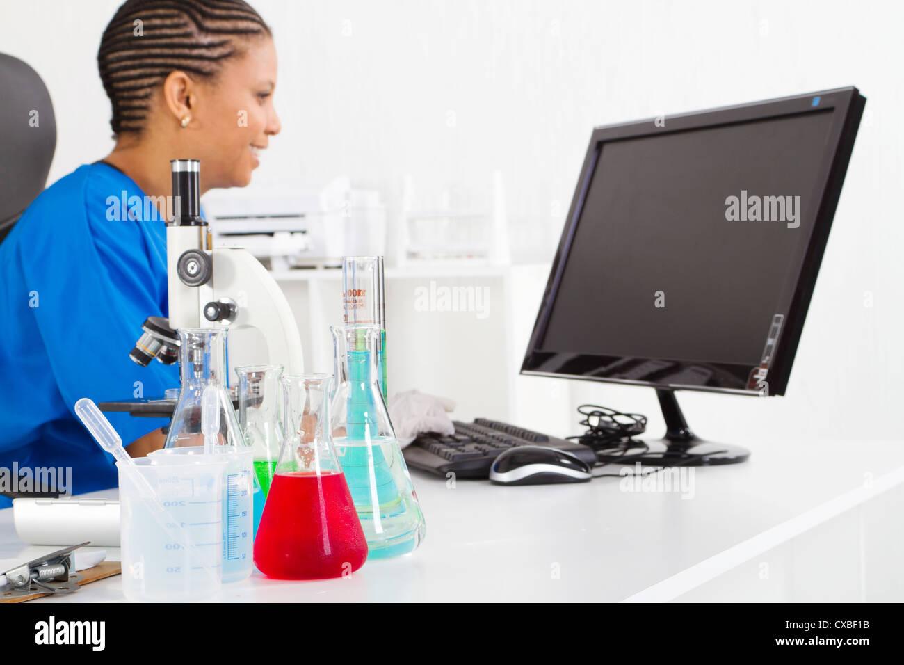 Mujer africana American Scientist en laboratorio, se centran en el líquido en la parte delantera Foto de stock