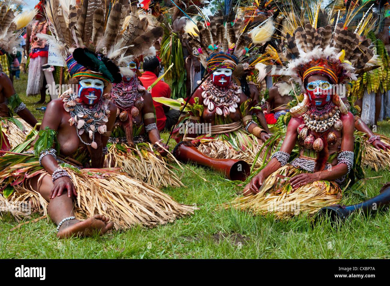 Vestimentas coloridas y la cara pintada de las tribus locales celebra la tradicional Sing Sing en las tierras altas Imagen De Stock