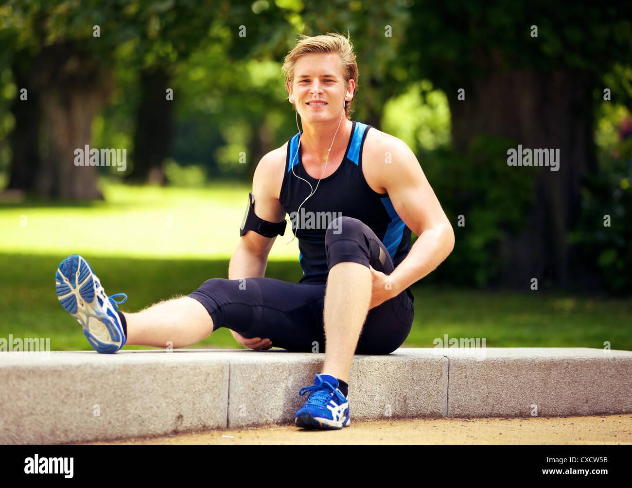 Cute athletic guy tomando su descanso después del ejercicio Imagen De Stock