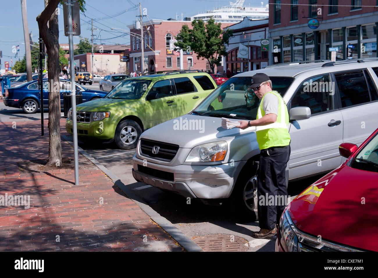 Traffic warden emite un ticket de aparcamiento en el centro de Portland, Maine, Estados Unidos. Foto de stock