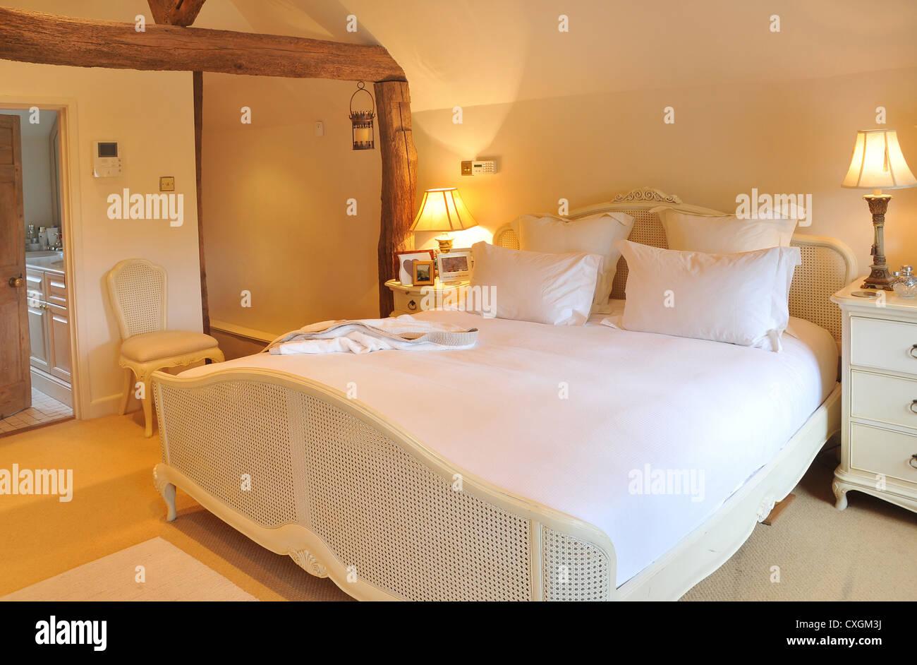 El diseño interior de dormitorio de un cottage ingles con cama, armarios de cabecera, luces, sillas y baño Imagen De Stock