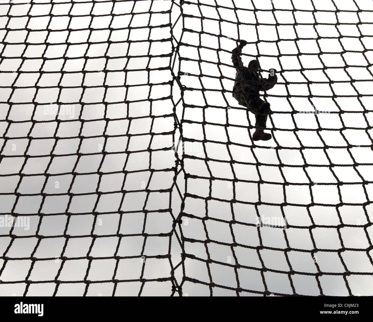 Una mujer recluta del ejército sube una escalera de cuerda en Victoria Torre durante el entrenamiento de combate Imagen De Stock