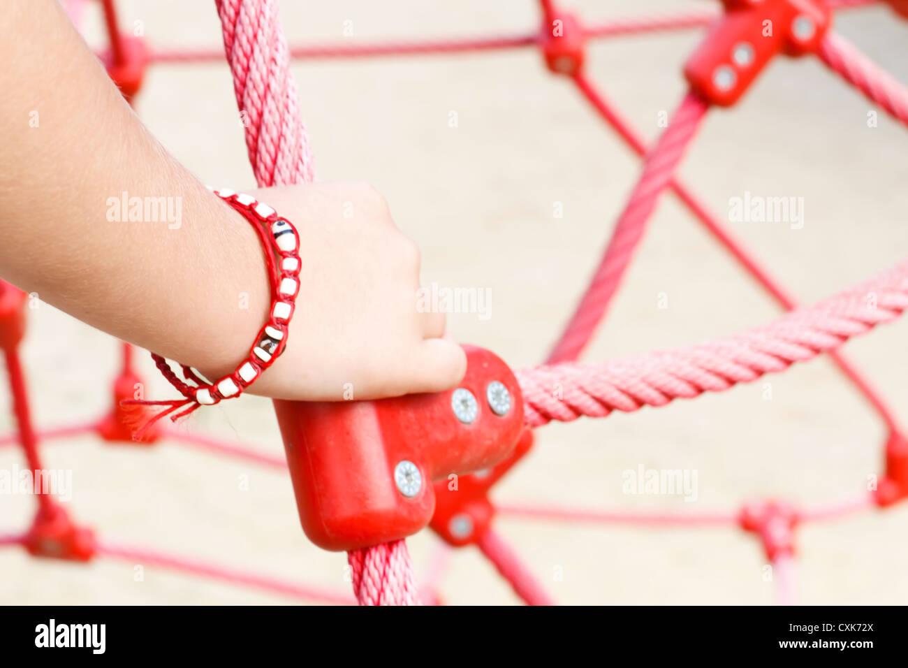 Chico's (6-7) mano sujetando la cuerda roja, Francia. Imagen De Stock