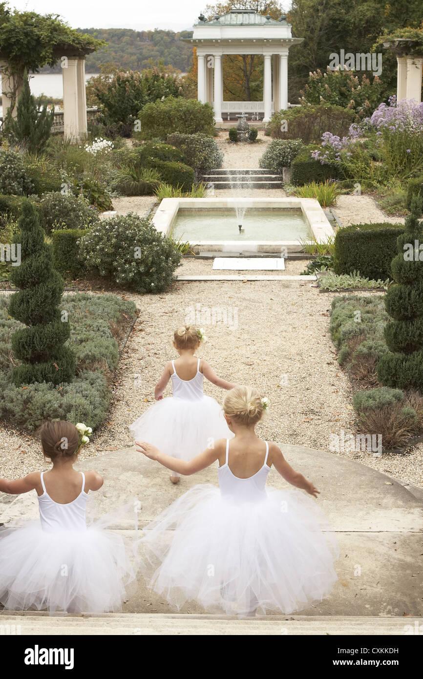 Las niñas en trajes de ballet ejecutando a través de jardín Imagen De Stock