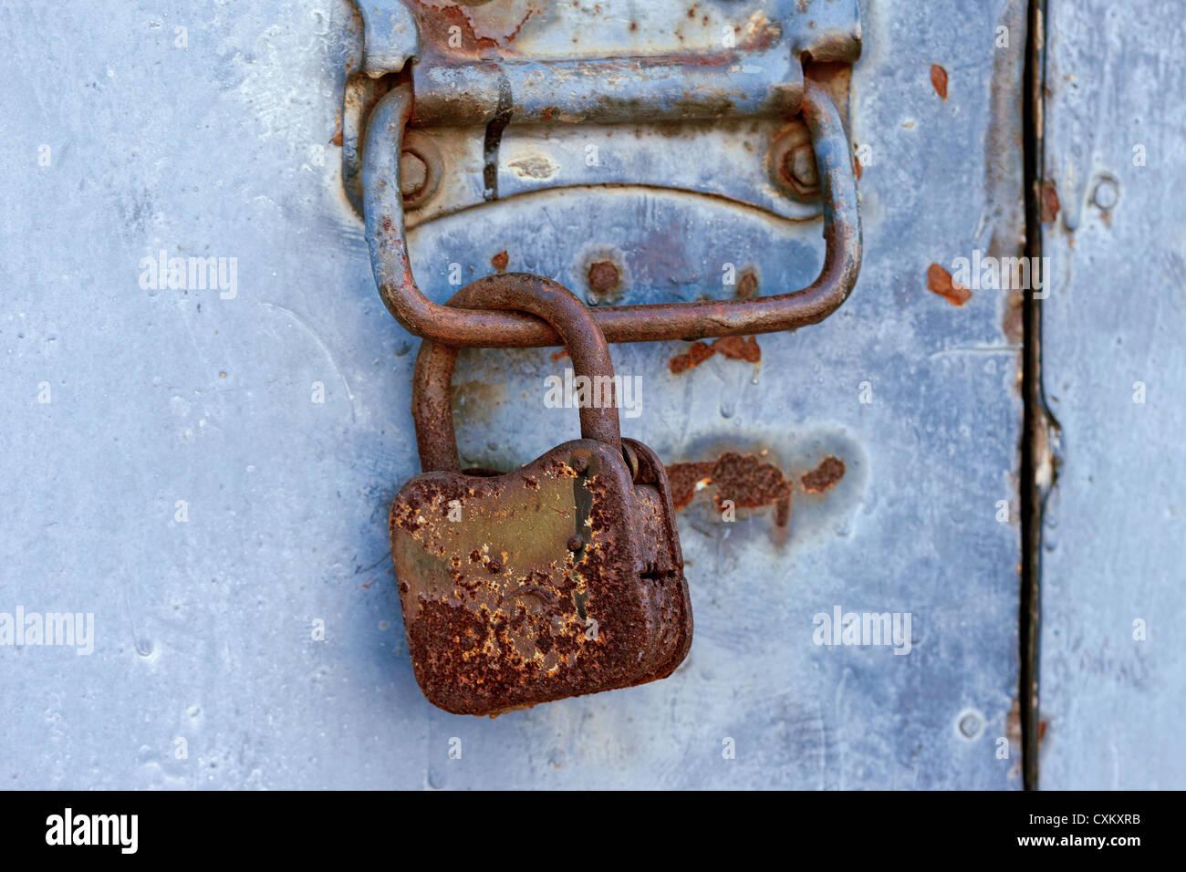 Rusty candado en una antigua puerta de metal Foto de stock