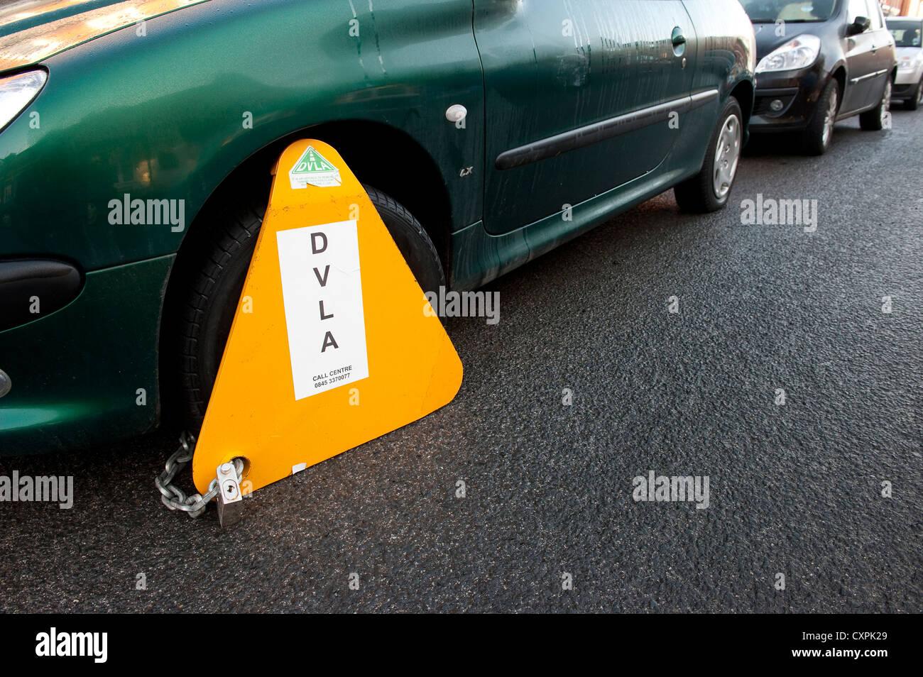 Abrazadera sobre una rueda de DVLA gratuitas coche aparcado en una calle en Inglaterra. Imagen De Stock