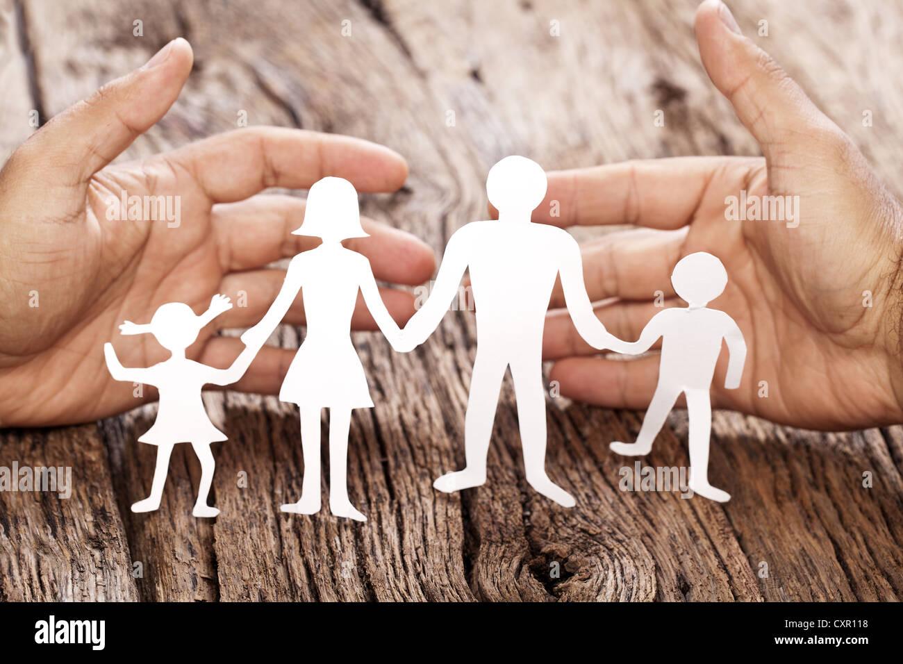 Figuras de cartón de la familia en una mesa de madera. El símbolo de la unidad y de la felicidad. Abrazo Imagen De Stock