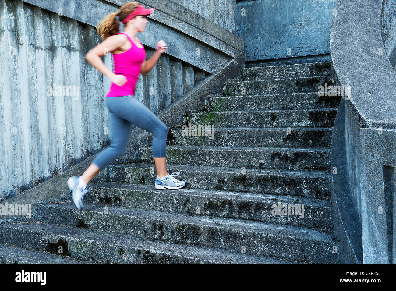 Mujer joven corriendo escaleras Imagen De Stock