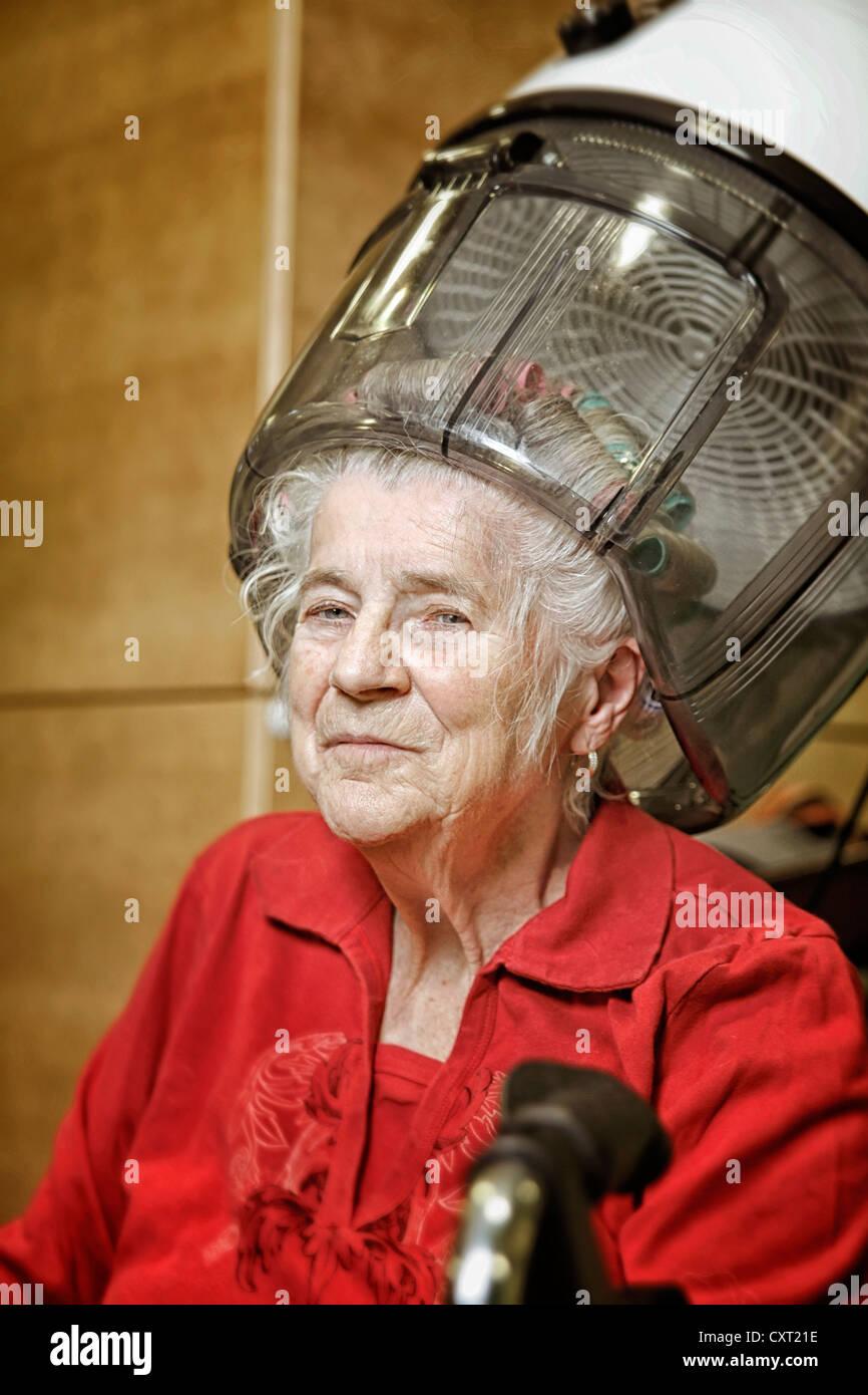 Mujer vistiendo rizadores de pelo con capucha Imagen De Stock