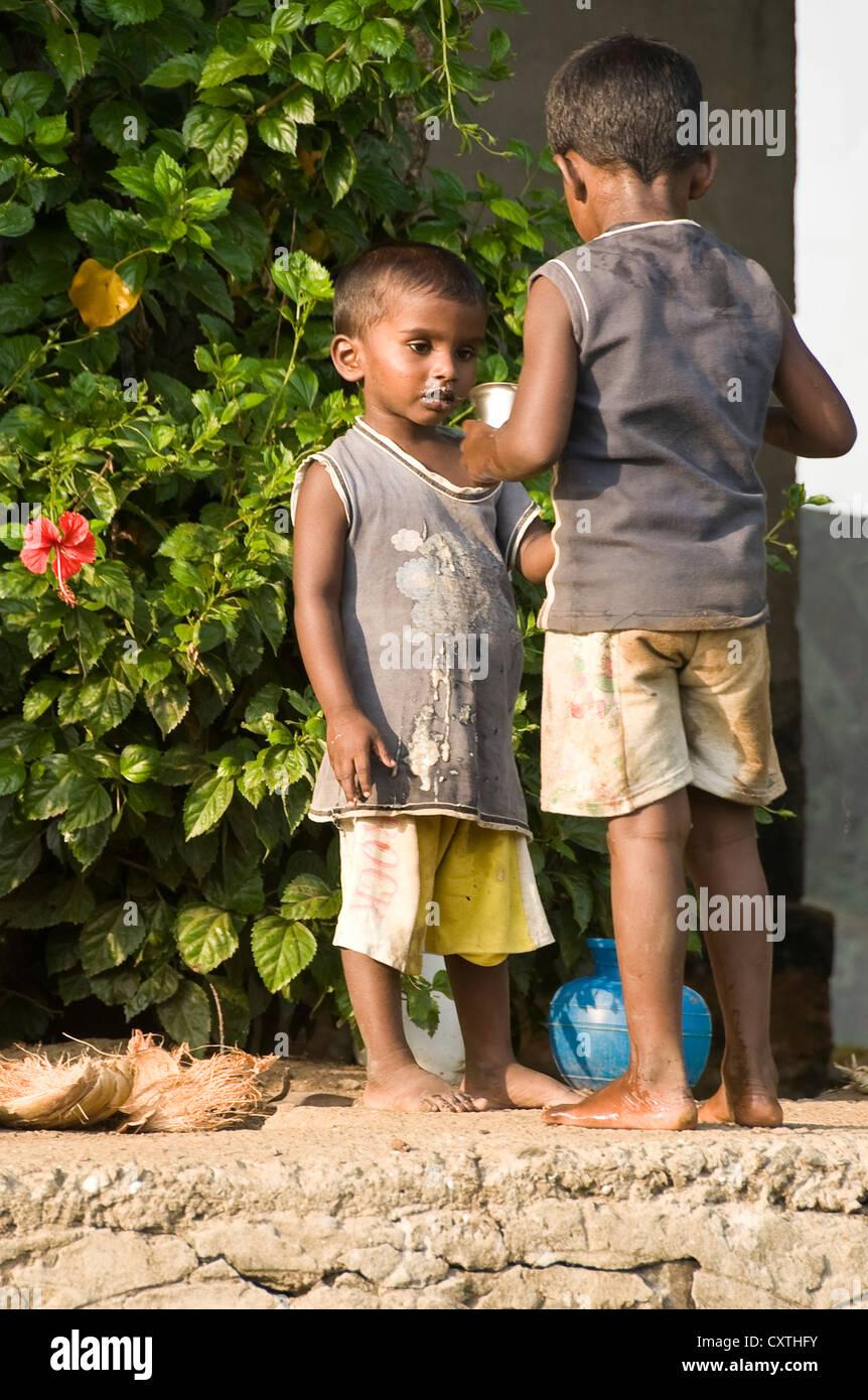 Vertical de dos pequeños niños indios cepillar sus dientes en la orilla del río en Kerala. Imagen De Stock
