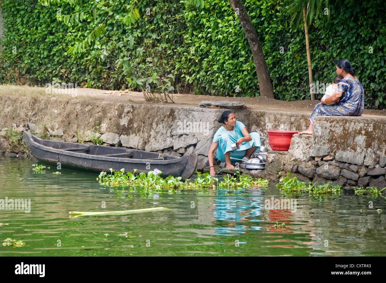 Horizontal retrato de una familia india haciendo sus tareas diarias en la orilla del río en Kerala. Imagen De Stock