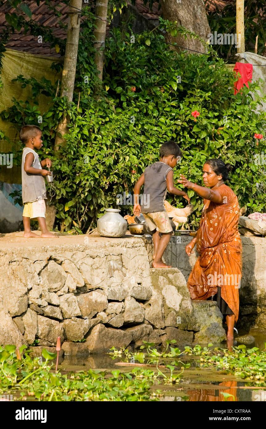 Vertical de una familia india haciendo sus tareas diarias, incluyendo obtener lavados por la Riverside en Kerala. Imagen De Stock
