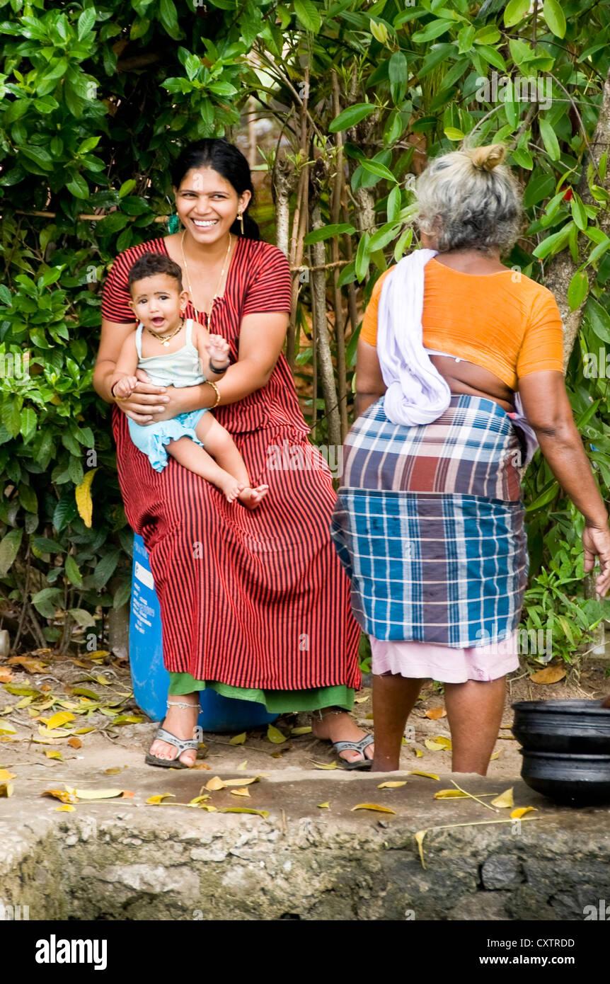 Vertical de tres generaciones de una familia india haciendo sus tareas diarias en la orilla del río en Kerala. Imagen De Stock