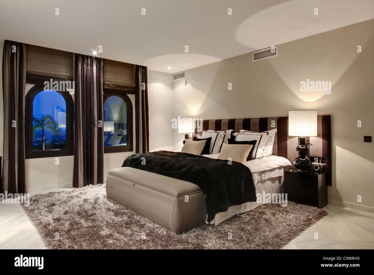 Cama y ventanas de dormitorio moderno Imagen De Stock