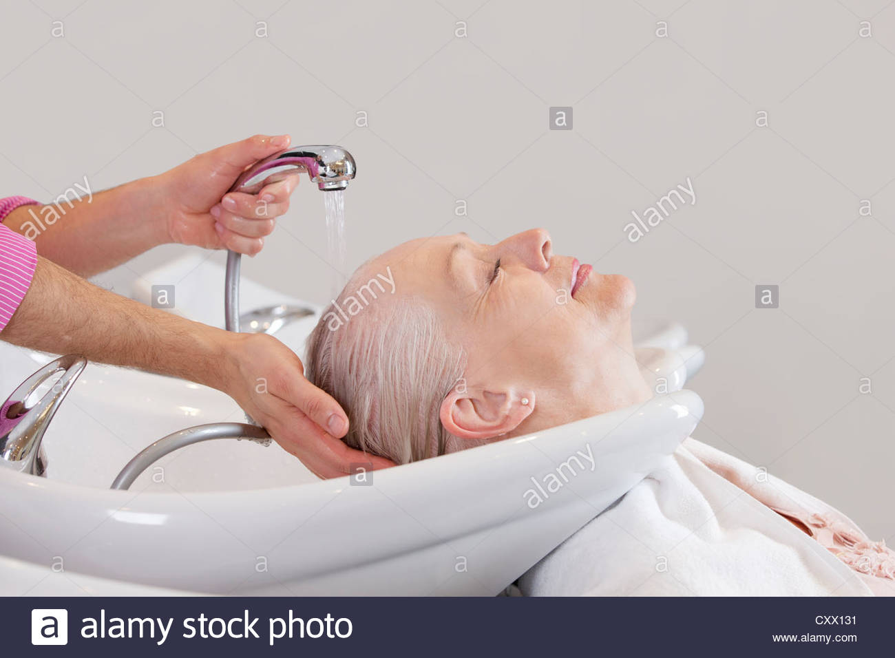 Una mujer mayor con sus cabellos lavados en peluquería, cerrar Imagen De Stock