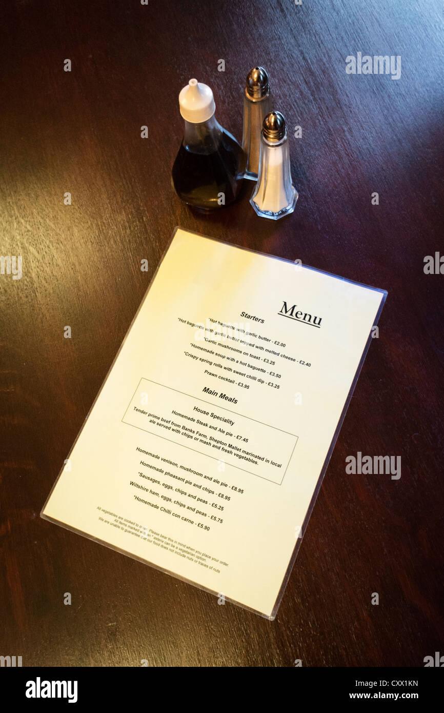 Menú y condimentos en una mesa de restaurante pub Imagen De Stock