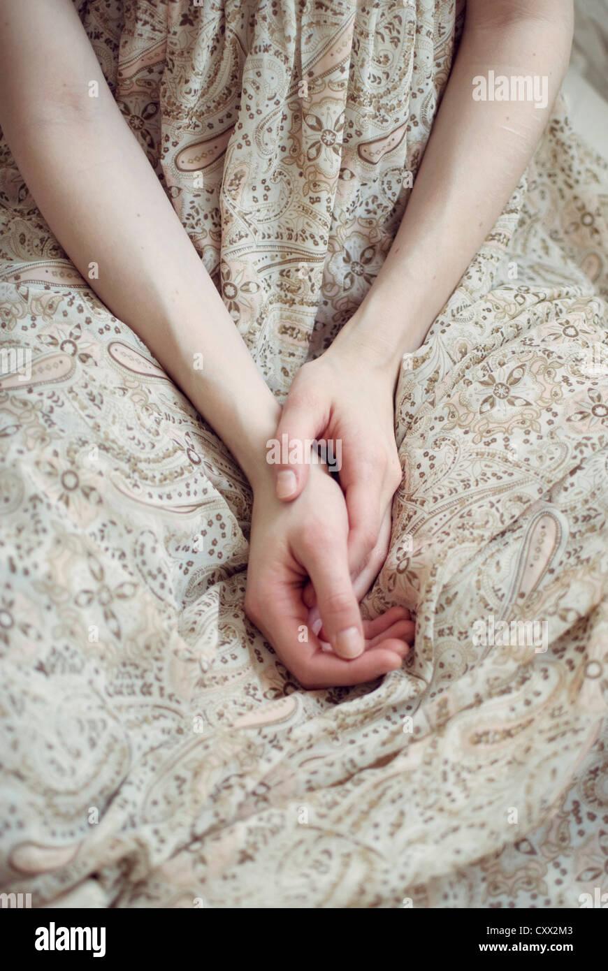 Cerrar foto de manos en el regazo de una chica que llevaba un vestido veraniego de luz Imagen De Stock