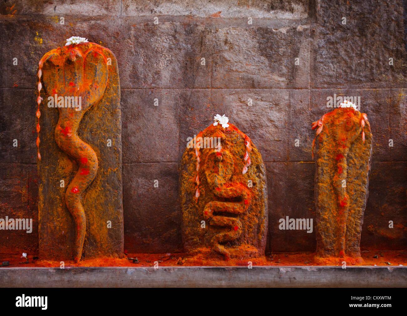 Tallas de serpientes, apoyada contra una pared rociado con polvos de colores, Mysore, India Foto de stock