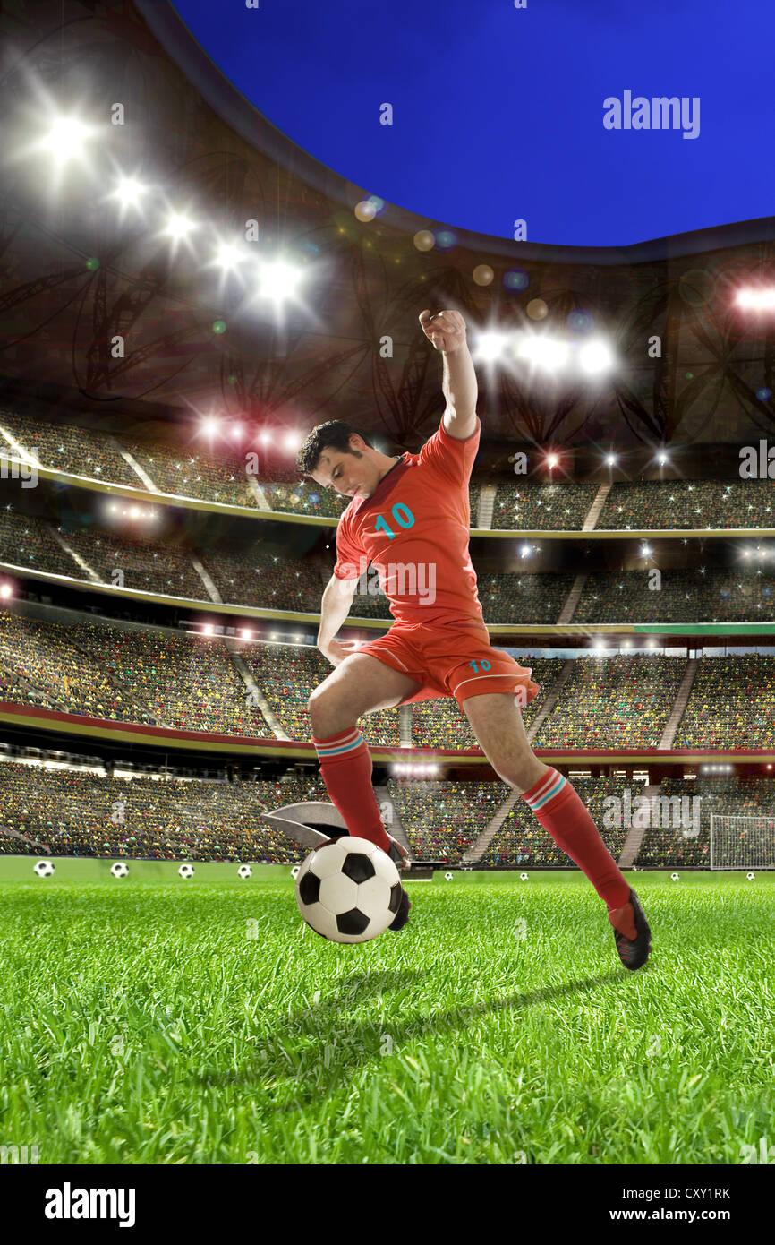 Jugador de fútbol pateando una pelota de fútbol, el estadio de fútbol Foto de stock