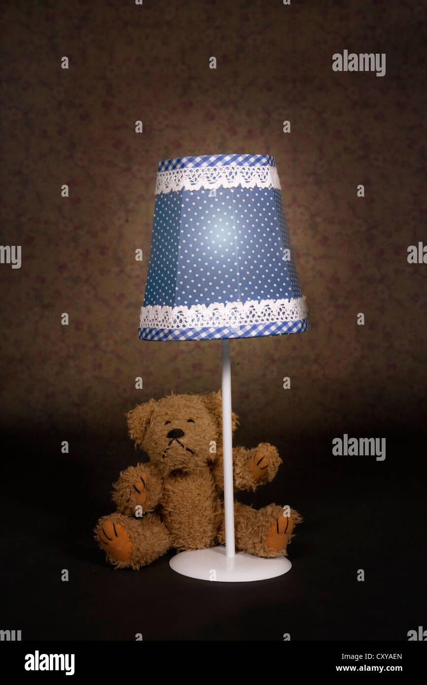 Un oso de peluche sentado en una vieja lámpara vintage Imagen De Stock