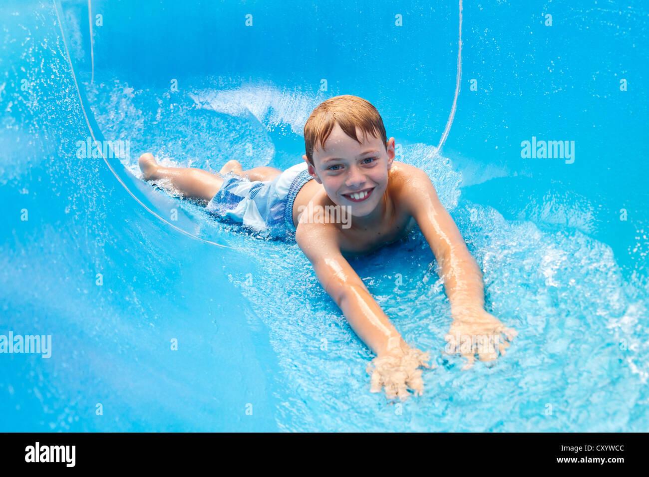 El muchacho, de 10 años, en un tobogán de agua en la piscina Imagen De Stock