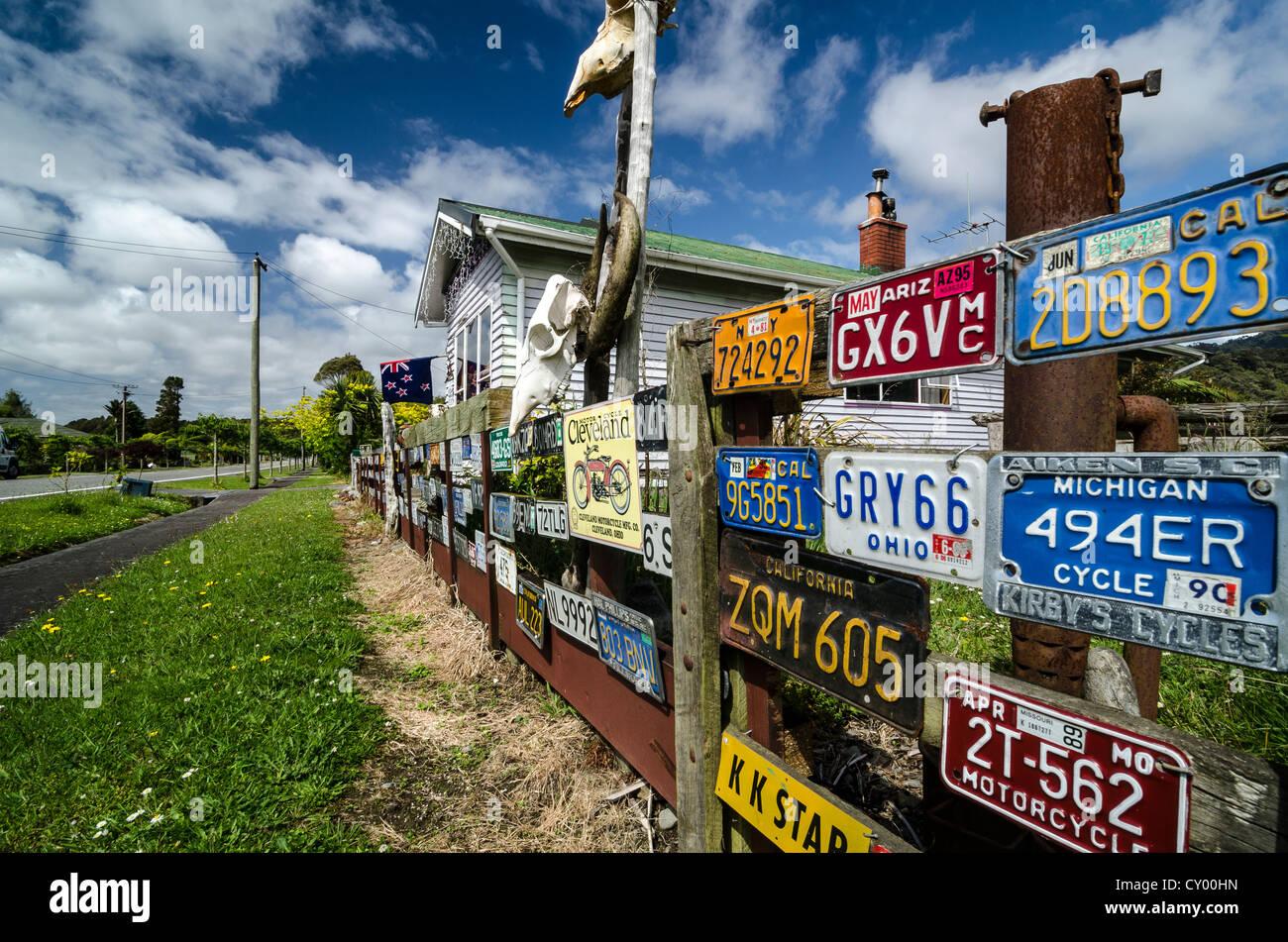 Muchas placas de matrícula estadounidense y cráneos en una valla de madera, Isla del Sur, Nueva Zelanda Imagen De Stock