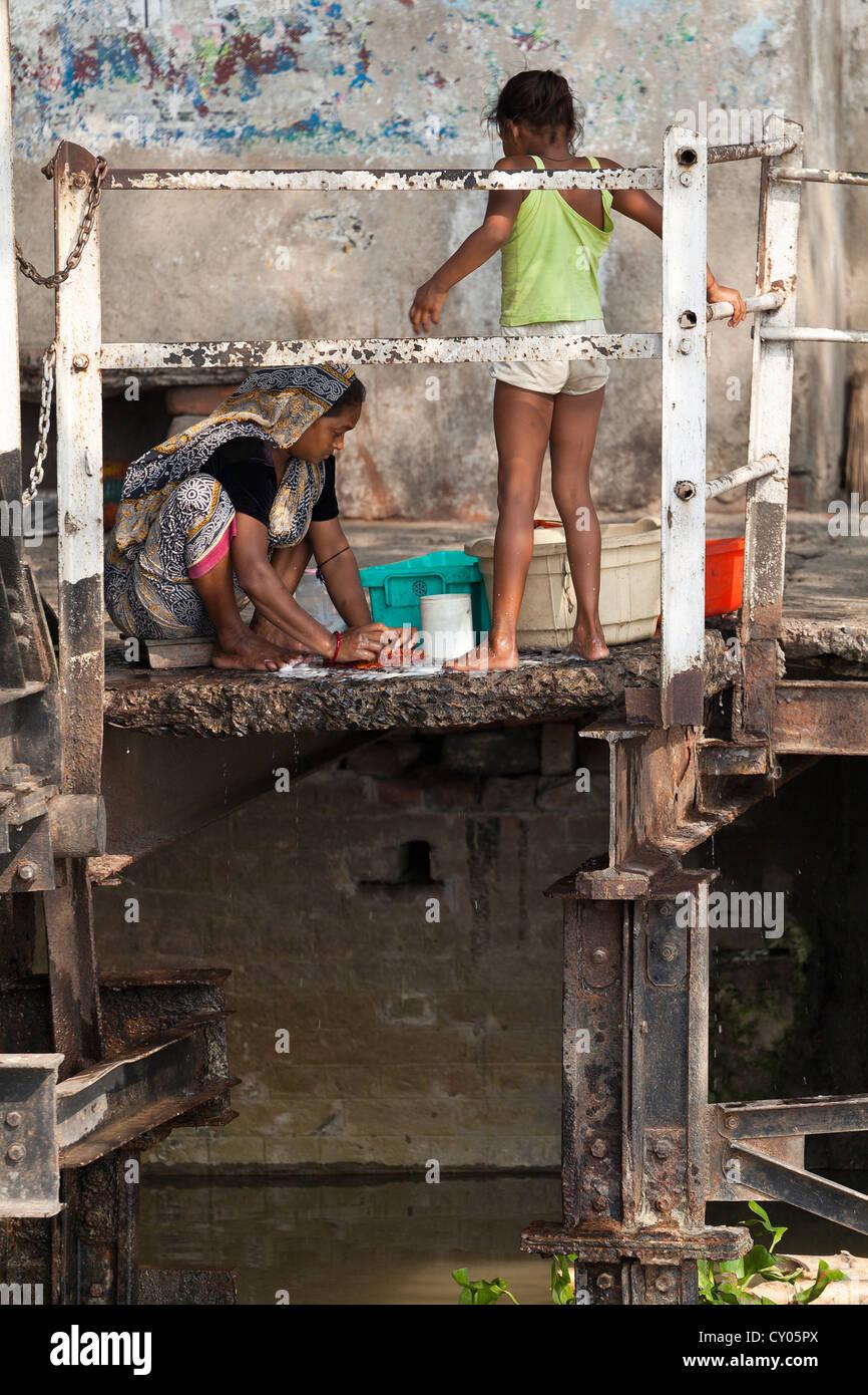 La madre y la niña lavando ropa en las orillas del río en Kolkata, India Foto de stock