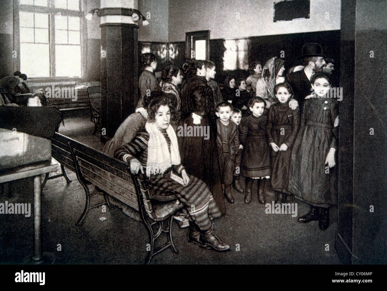 Grupo de emigrantes esperando en la pluma de detención después de pasar sus exámenes de ingreso, Ellis Island, Nueva Foto de stock