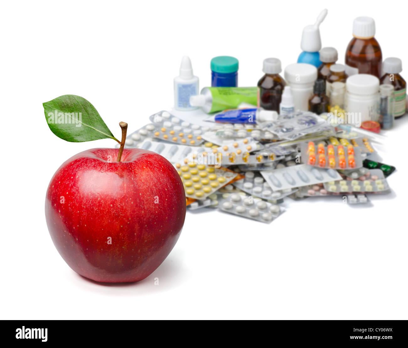Manzana roja en frente de una gran pila de medicamentos. Concepto de estilo de vida saludable. Imagen De Stock