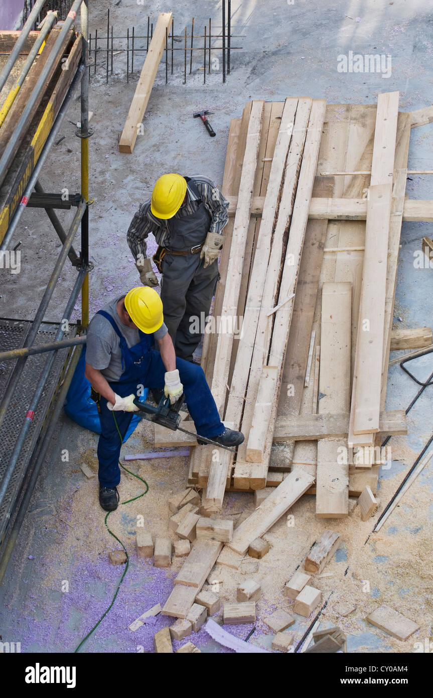 Los trabajadores de la construcción de corte de madera para el embarque con una motosierra, PublicGround Imagen De Stock