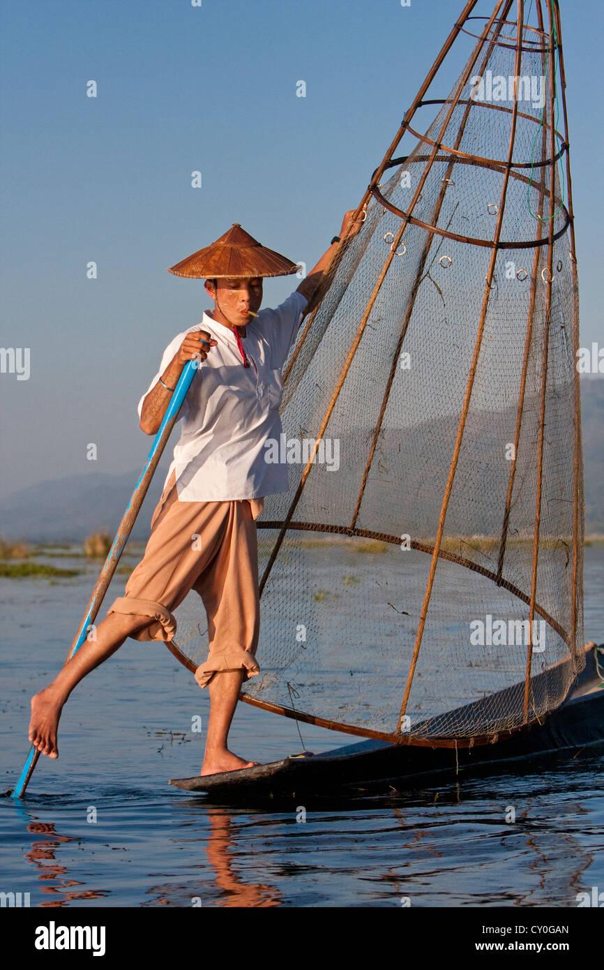 Myanmar, Birmania. Pescador en busca de un lugar para establecer su red, mientras que el remo con una pierna, en Imagen De Stock