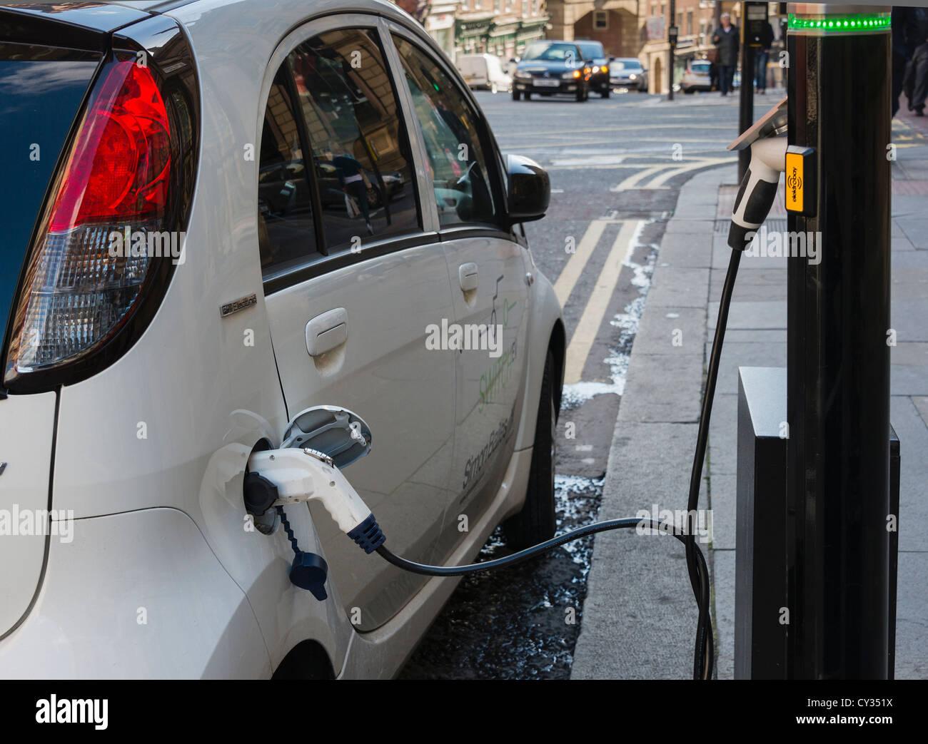 Coche eléctrico en la calle del punto de carga Imagen De Stock