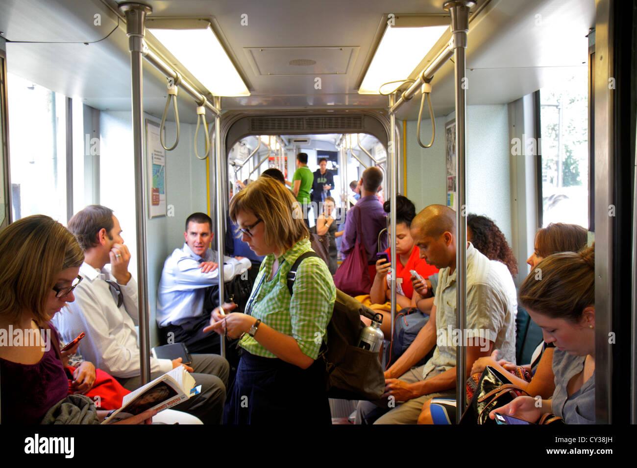 Boston Massachusetts MBTA T línea verde del metro tren entrante riders hombre mujer comprobación de lectura Imagen De Stock