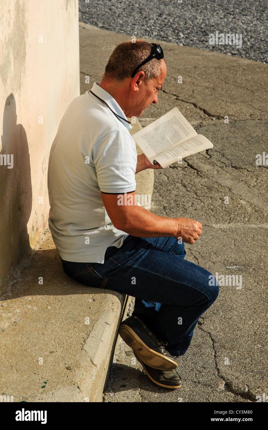 Hombre leyendo el libro - El pájaro artista por Harward Norman, Camogli, Italia Imagen De Stock