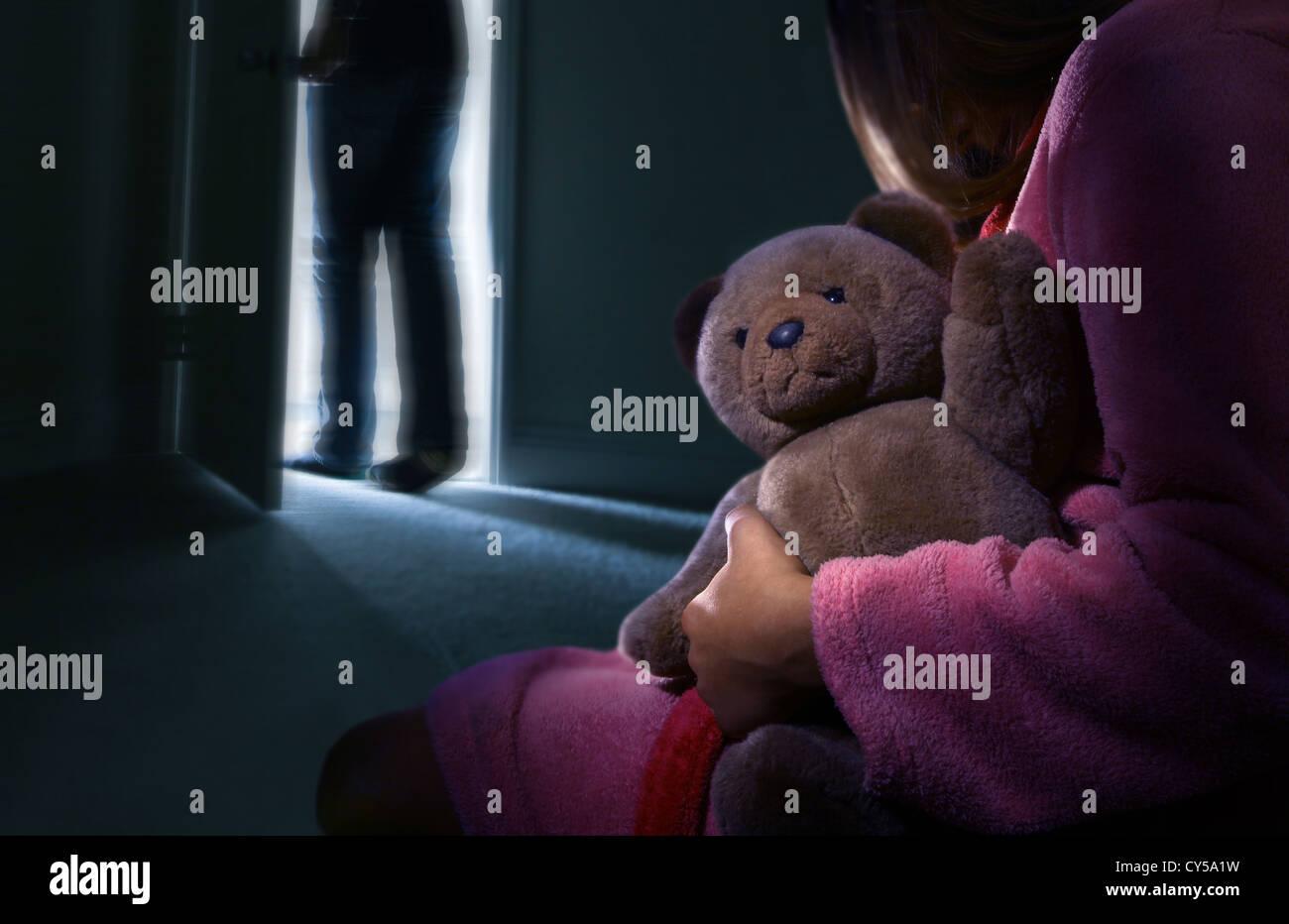 Vista posterior si un niño en una habitación oscura sosteniendo un oso de peluche, un hombre acaba de Imagen De Stock