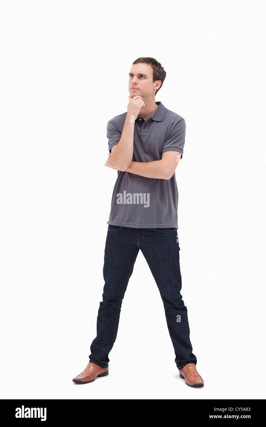 Pensativo hombre de pie y sus piernas separadas Imagen De Stock