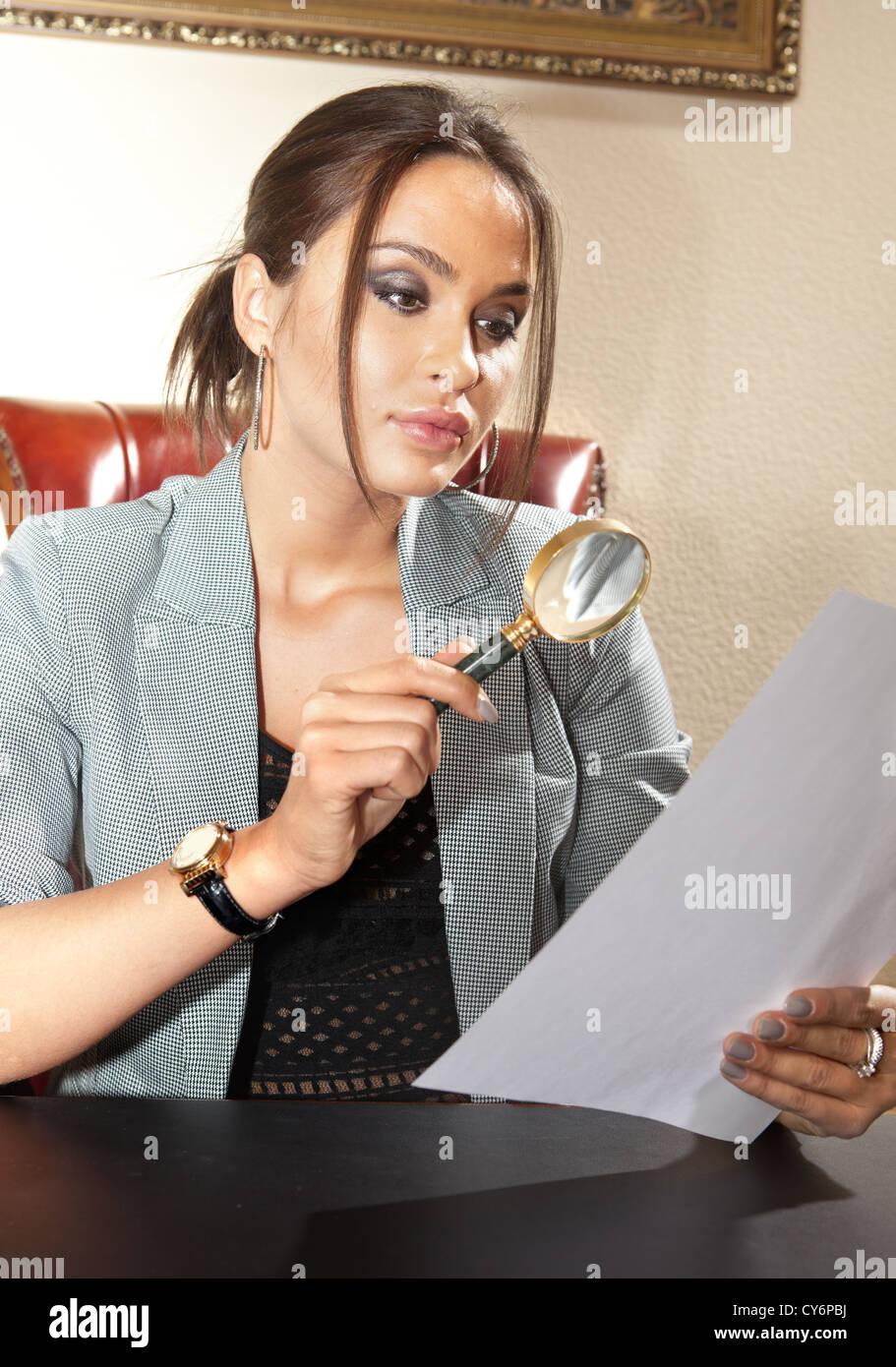 Mujer de negocios que se ve en un documento con lupa Imagen De Stock