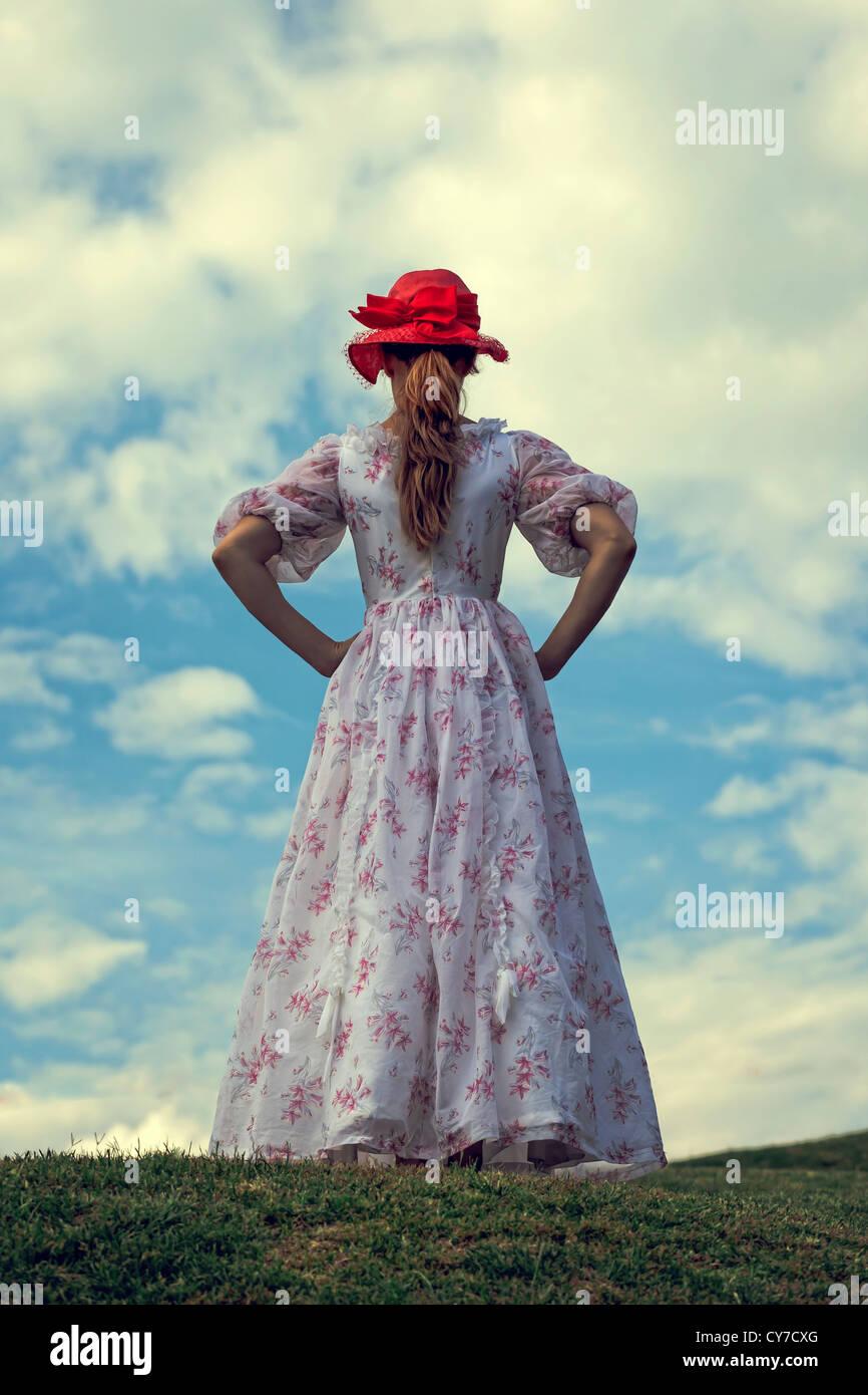 Una mujer en un vestido de flora y una red hat se está ejecutando en un prado Foto de stock
