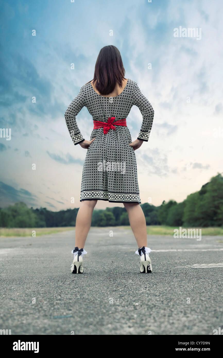 Una mujer en un vestido blanco y negro está de pie sobre una calle Foto de stock