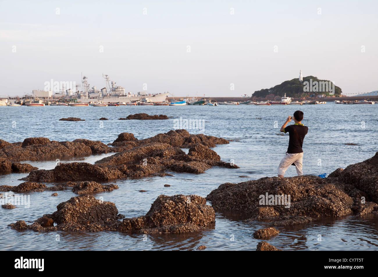 5162b60b83d26 Un turista toma una foto de un destructor chino anclados en la bahía de  Qingdao