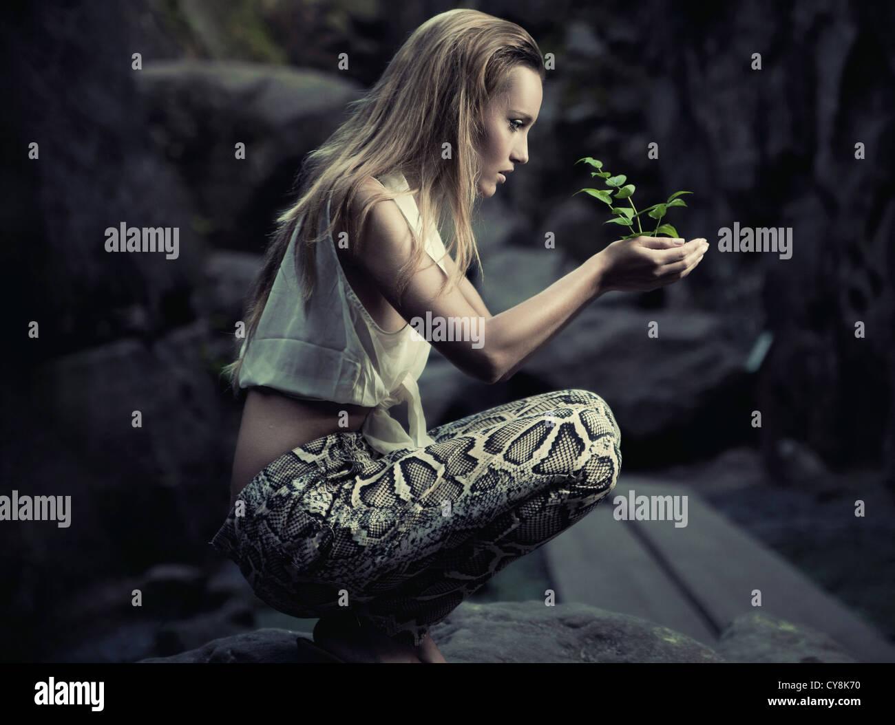 Hermosa joven sosteniendo una planta Imagen De Stock